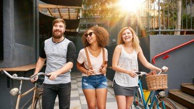 Três pessoas sorrindo e caminhando com bicicletas