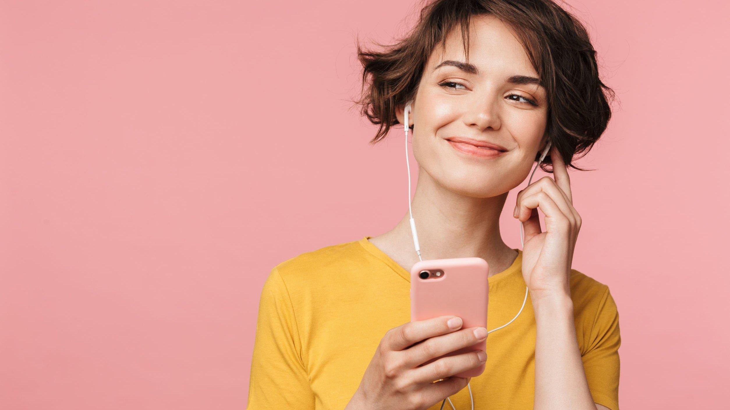 Mulher ouve música em fone de ouvido conectado a celular.