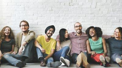 Grupo de amigos sentados no chão, lado a lado, sorrindo