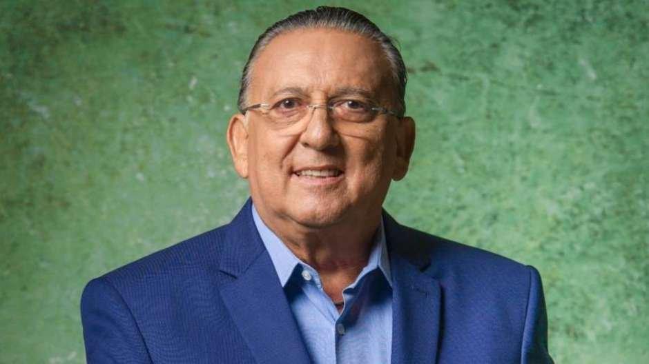 Galvão Bueno posando para foto em estúdio com fundo verde.