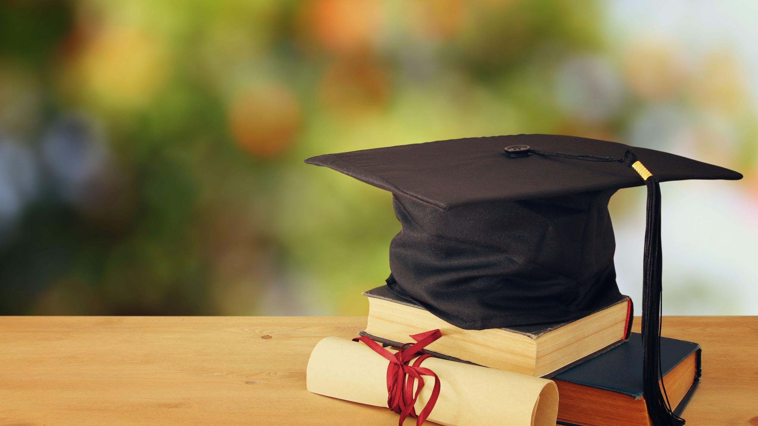 Chapéu de formatura em cima de livros e ao lado do canudo com certificado