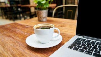 Xícara de café com ilustração de sol e nuvens em um papel atrás