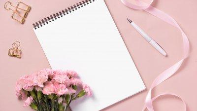 Caderno e caneta ao lado de um buquê