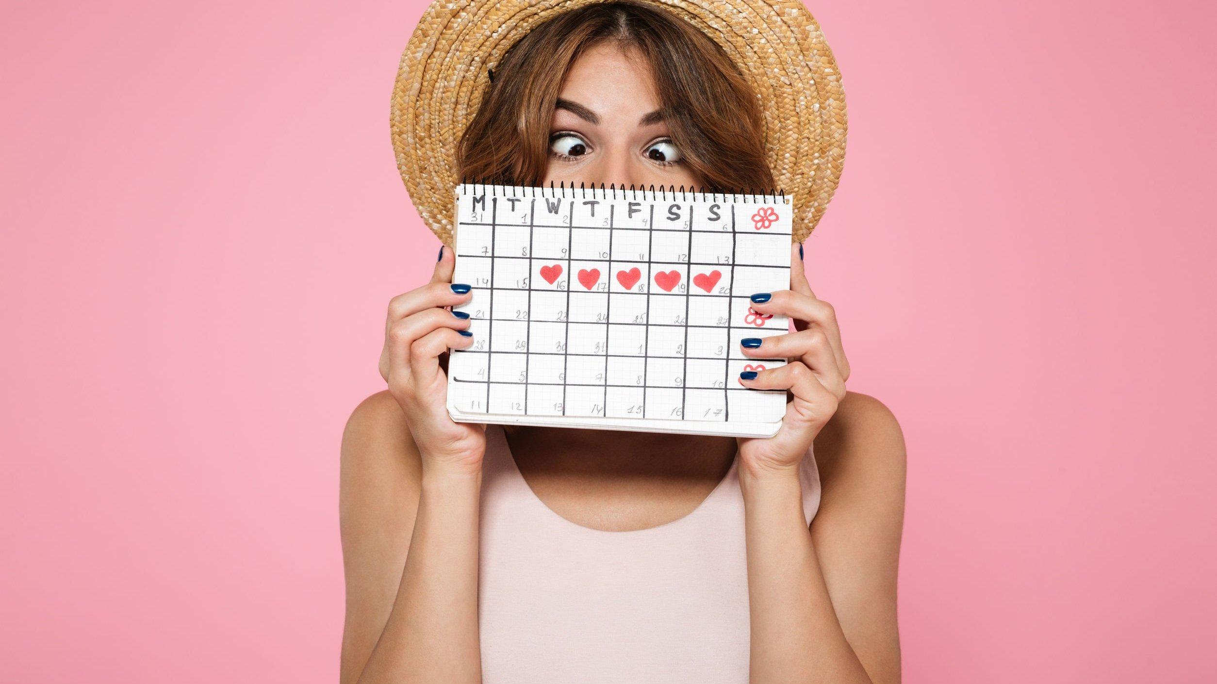 Mulher segurando um calendário cobrindo o rosto