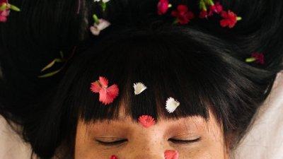 Mulher de olhos fechados com petadas de flor em seu rosto