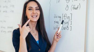 Professora apontando para lousa com caneta