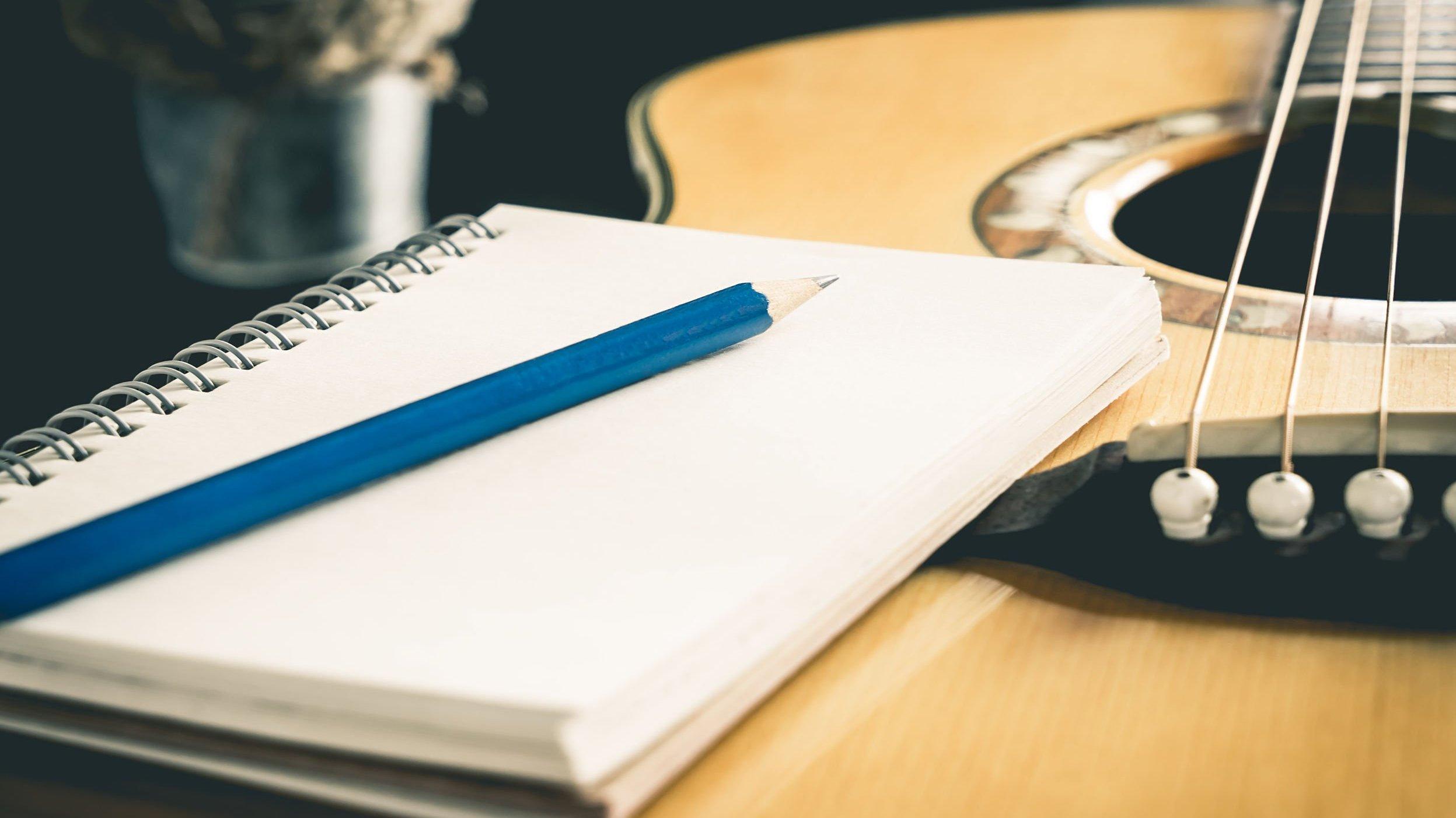 Caderno branco aberto com lápis em cima sobre um violão.