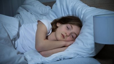 Menina branca dormindo numa cama