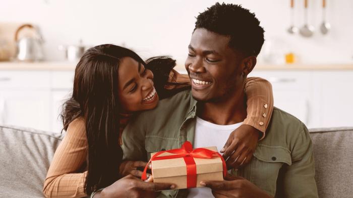 Namorada segurando presente e fazendo surpresa de aniversário para namorado