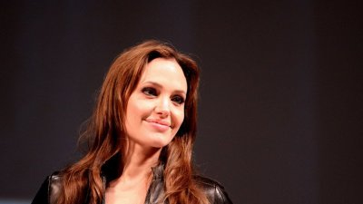 Angelina Jolie sentada em frente a um microfone em um evento.