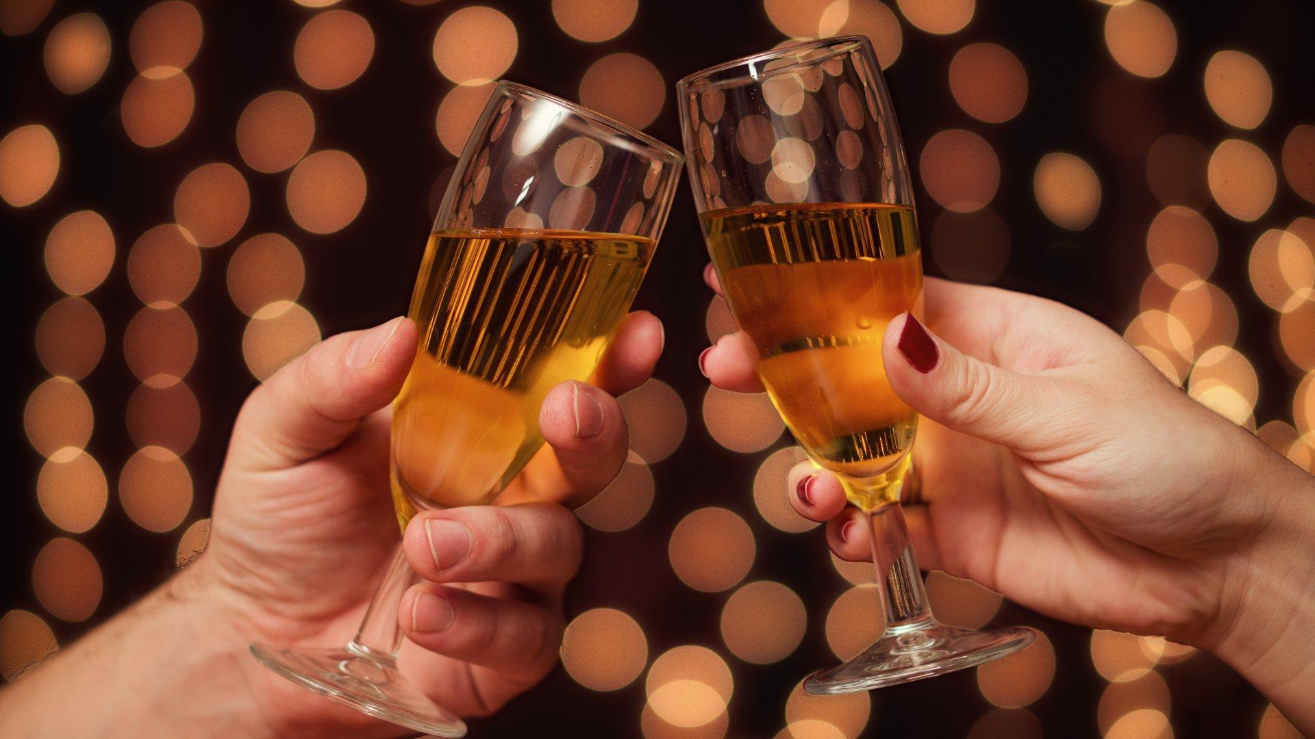 Foco na mão de pessoas brindando taças no ano novo