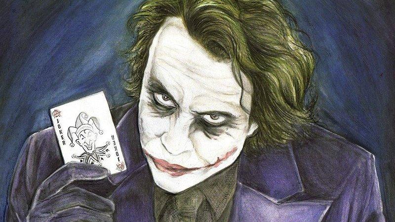 Imagem do personagem Coringa segurando uma carta de baralho na mão.