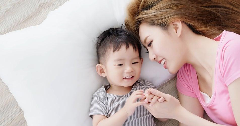 Mãe deitada ao lado de bebê