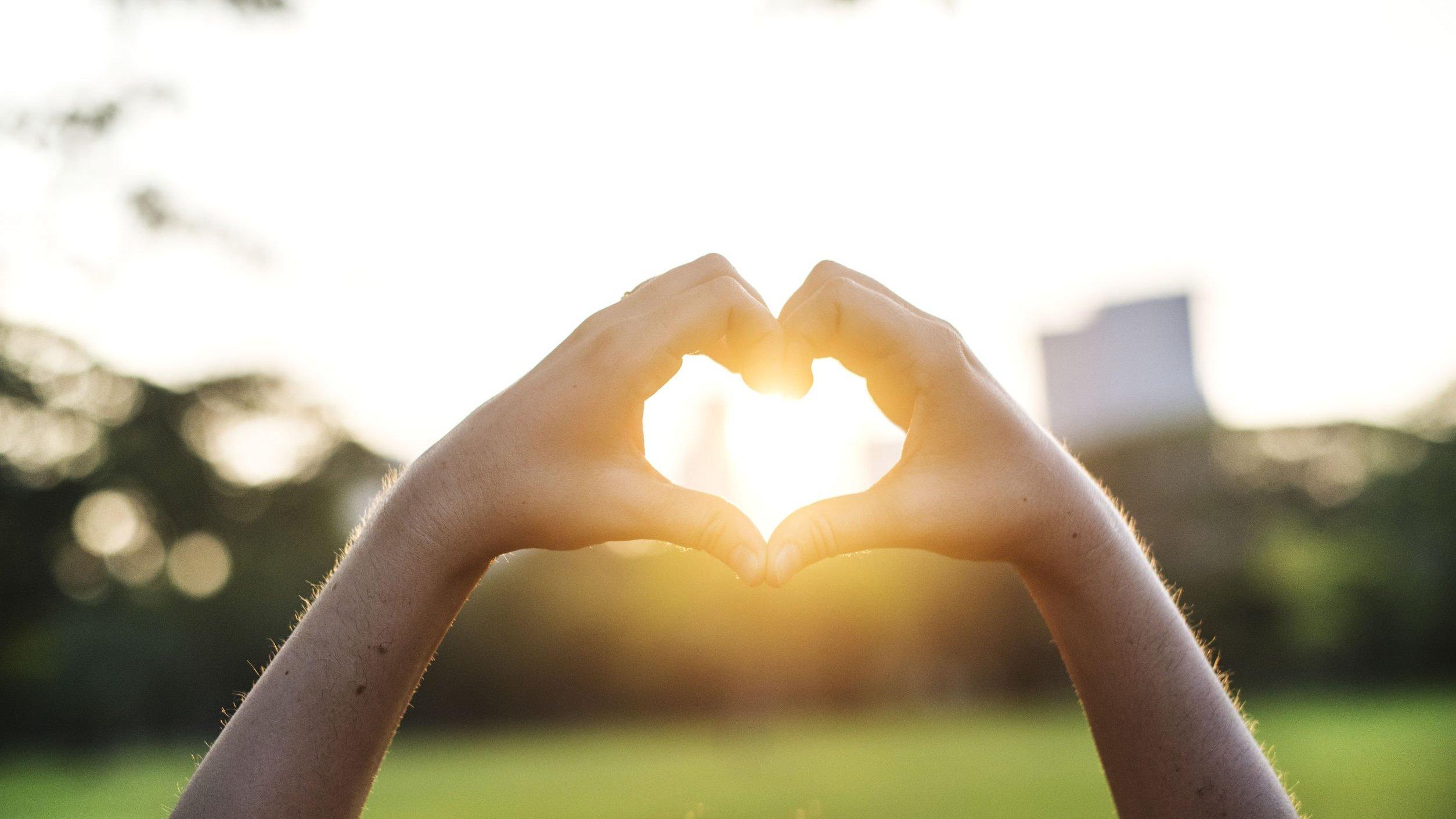 Pessoa fazendo um coração com as mãos em direção ao sol
