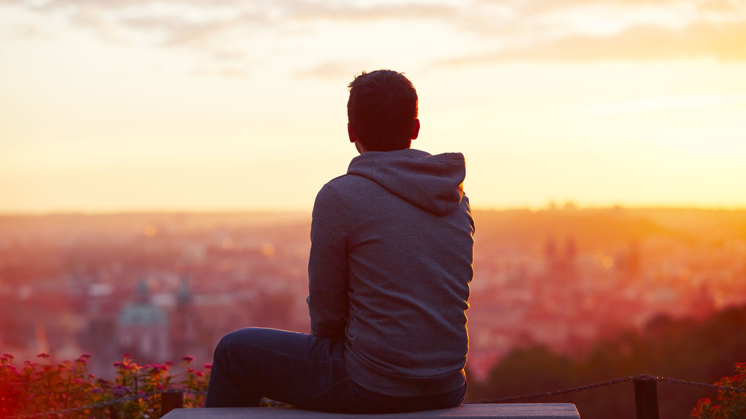 Homem olhando para o pôr do sol.