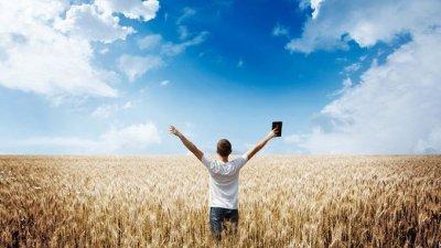 Garoto com braços abertos e bíblia em uma das mãos em campo aberto e céu azul