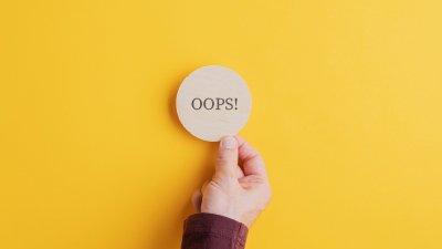 Mão segurando uma pequena placa com os escritos 'oops!'