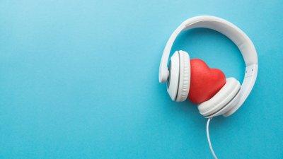 Fundo azul, com fone de ouvido branco, e um coração vermelho de borracha entre os dois lados do fone.