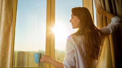 Mulher de costas abrindo a janela com sol refletindo