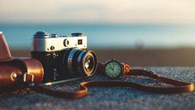 Câmera fotográfica repousada numa pedra com praia ao fundo.