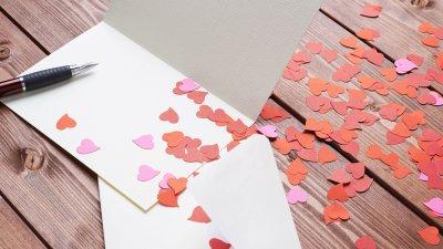 Carta e envelope em uma mesa com corações pequenos