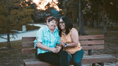 Mãe e filha sorrindo sentadas em banco de praça