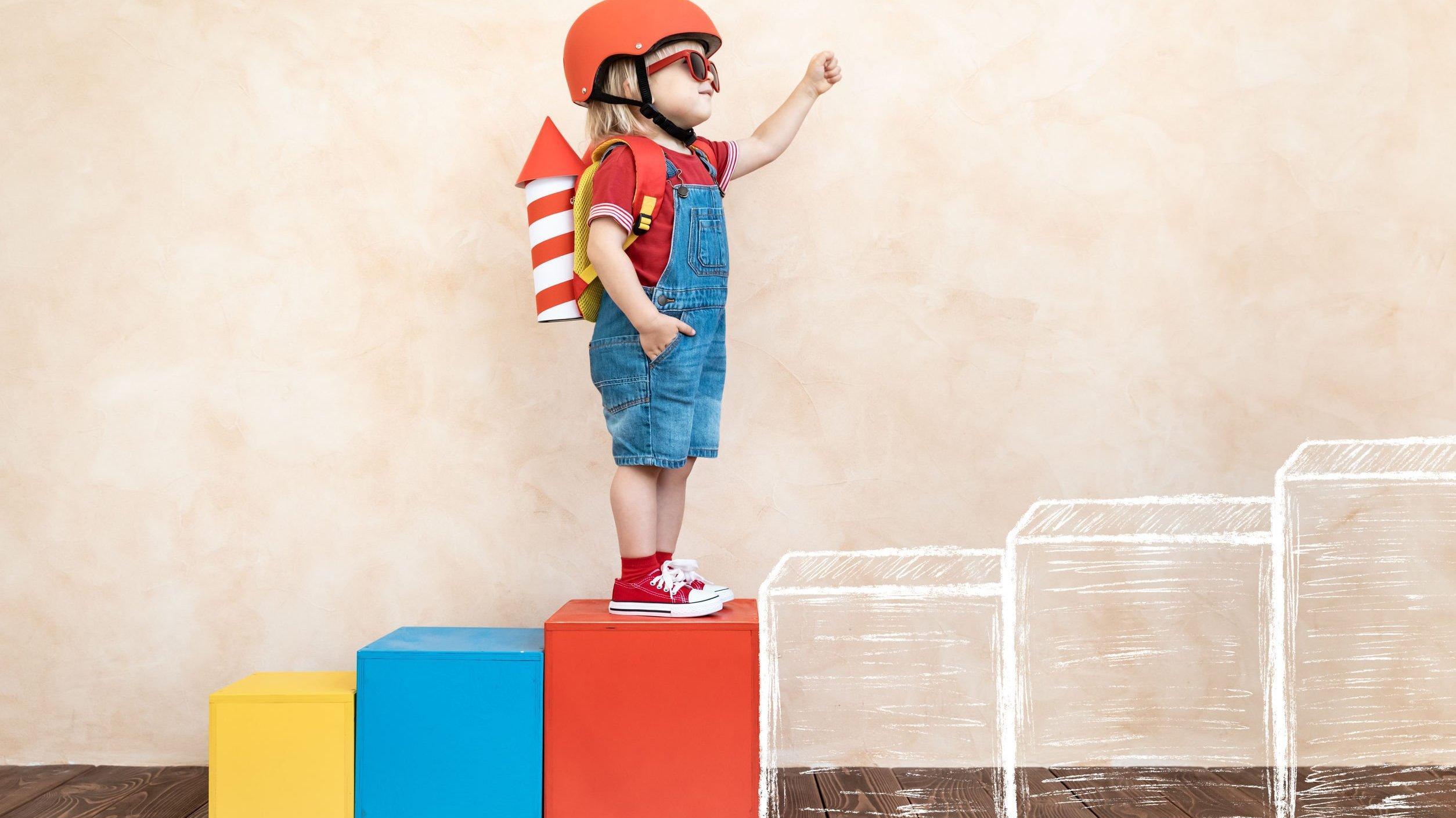 Menino branco e loiro em cima de bloco vermelho.