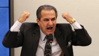 Silas Malafaia gritando em microfone de mesa com os dois punhos fechados dos dois lados de sua cabeça.