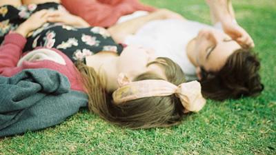 Casal deitado na grama.