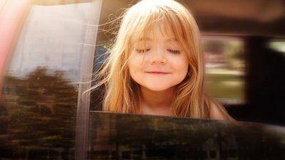 Menina sorrindo com olhos fechados em carro