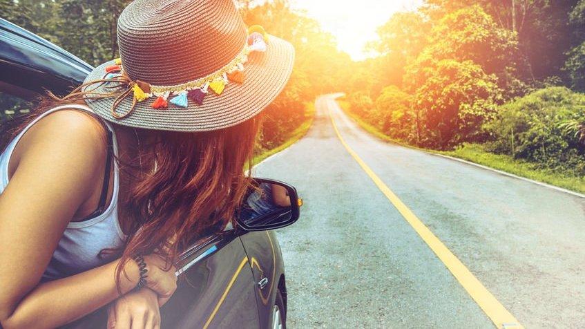Mulher com meio corpo para fora da janela do carro com chapéu olhando para estrada