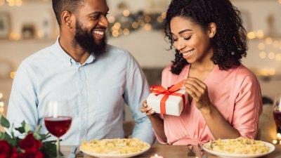 Homem entregando caixa de presente para mulher, que sorri para o presente com a mão esquerda no rosto.