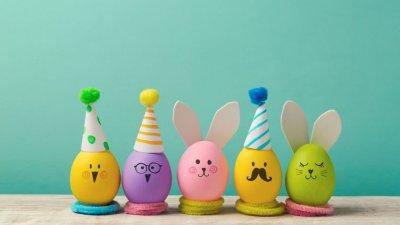 Ovos de galinha coloridos com desenhos de rostos, chapéus e orelhas de coelho