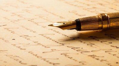 Caneta tinteiro repousando sobre uma folha de papel com escritas em caligrafia.