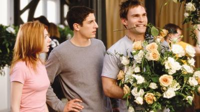 Michelle e Jim olhando para Stifler que segura um buquê de flores nos braços, e uma rosa entre seus dentes.