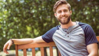 Homem sentado em banco de madeira