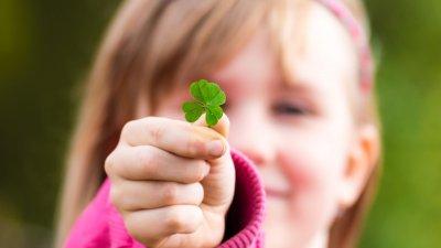 Criança segurando um trevo de quatro folhas