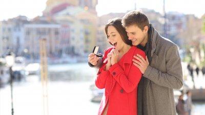 Homem entregando uma aliança de noivado à sua namorada, que se mostra surpresa