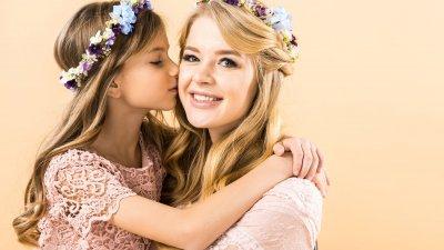 Filha beijando bochecha da mãe