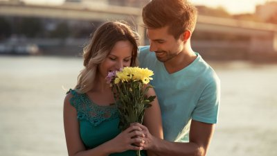 Homem atrás de mulher, a surpreendendo, colocando flores em sua frente.