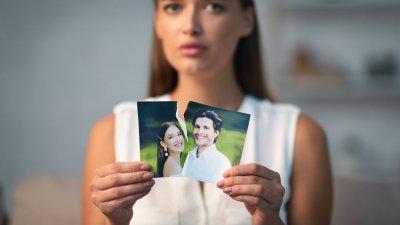 Mulher segurando uma foto rasgada dela com seu ex-namorado