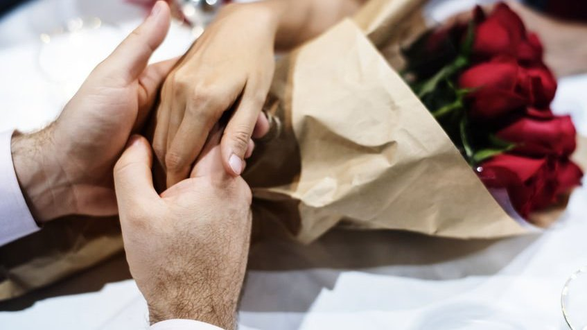 Homem e mulher de mãos dadas por cima de buquê de rosas