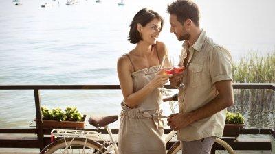 Casal brindando na praia.