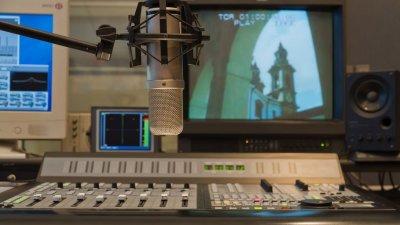 Foto de estúdio de gravação e dublagem com microfone, tv e botoões