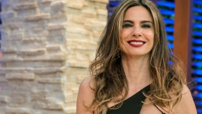 Luciana Gimenez sorrindo em programa de televisão.
