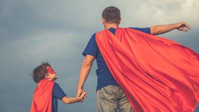 Pai e filho com roupas de super-herói, vistos de costas.