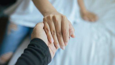 Pessoa segurando a mão de uma mulher.