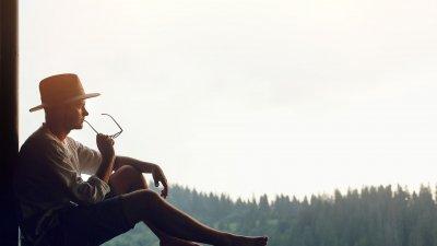 Homem sentado em janela grande com óculos na mão e chapéu refletindo