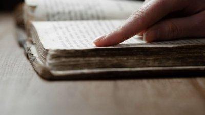 Bíblia com mão apontando versículos