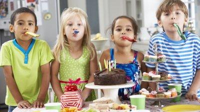 Quatro crianças lado a lado atrás de uma mesa de festa de aniversário, assoprando línguas-de-sogra.